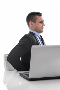 8347921-pain-businessman-sitting-with-backache-at-desk-isolated-on-white-background